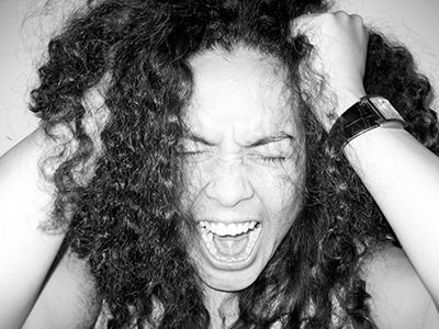 woman pulling her hair and screaming in frustration