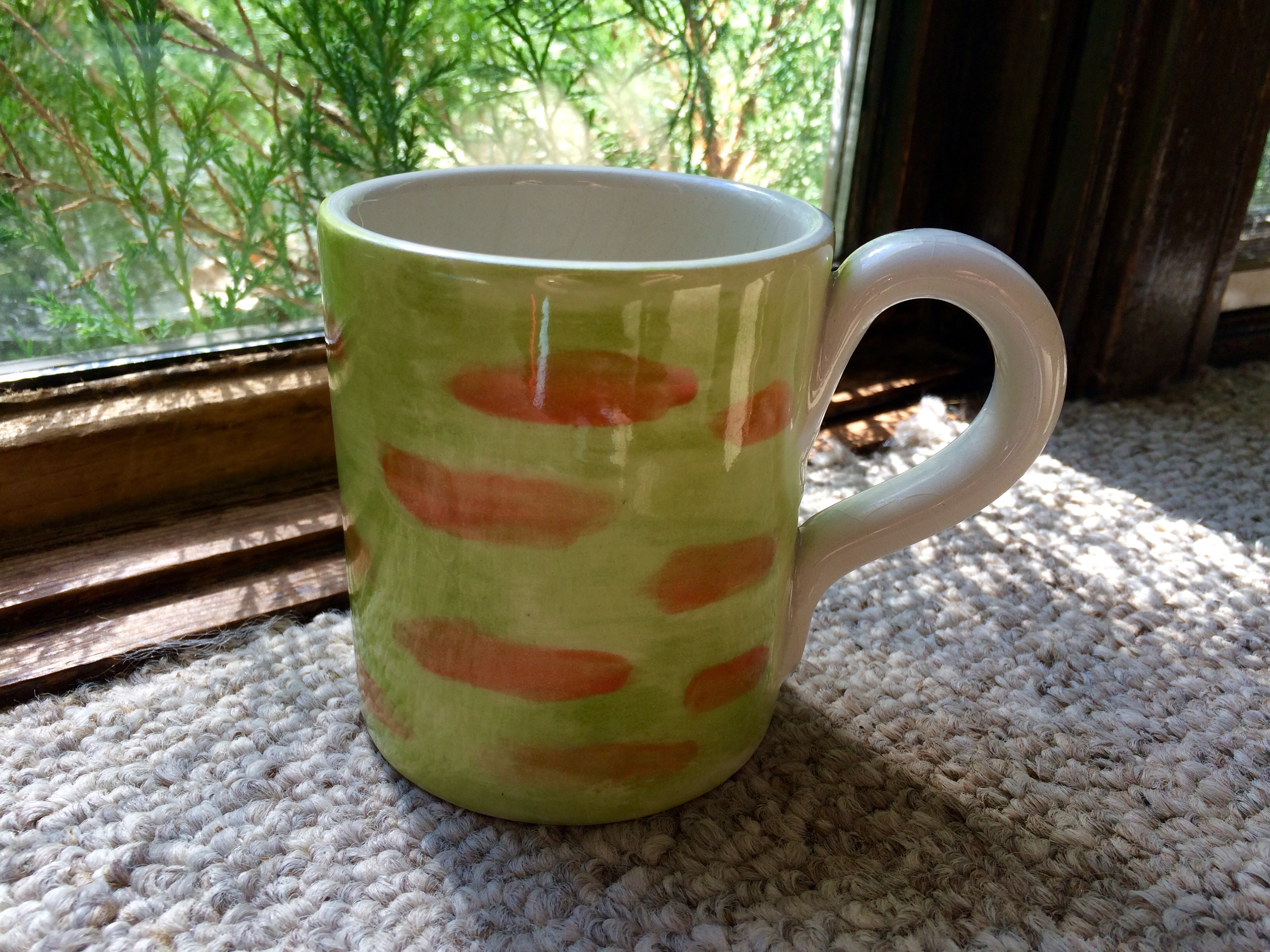 a poorly painted green coffee mug with orange stripes