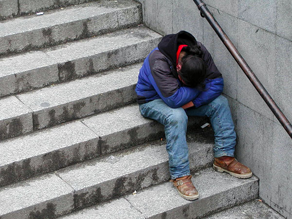 Homeless man sitting on stairs with head down